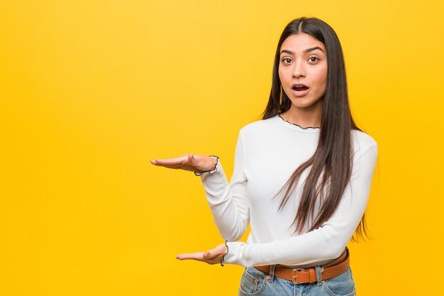 Giovane bella donna araba nei confronti di un giallo scioccato e stupito tenendo una a tra le mani.