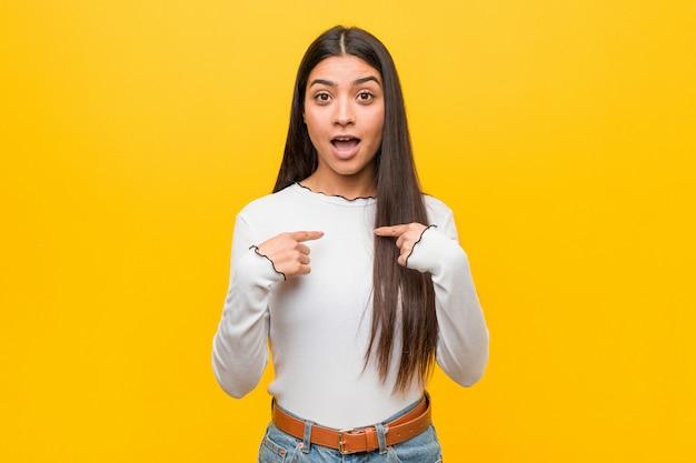 Giovane bella donna araba nei confronti di un giallo sorpreso indicando con il dito, sorridendo ampiamente.
