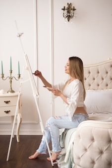 Giovane bella donna artista che dipinge a casa peonie rosa