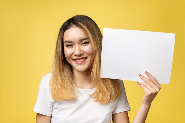 Giovane bella donna asiatica attraente dello studente che tiene libro bianco in bianco.