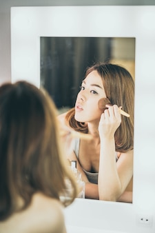 Giovane bella donna asiatica che fa trucco vicino allo specchio