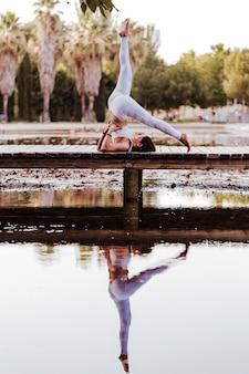 Giovane bella donna asiatica che fa yoga in un parco. seduto sul ponte con la riflessione sul lago d'acqua. yoga e concetto di stile di vita sano