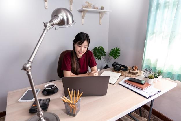 Giovane bella donna asiatica che lavora a casa