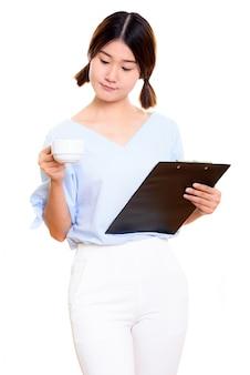 Giovane bella donna asiatica che tiene appunti e tazza di caffè