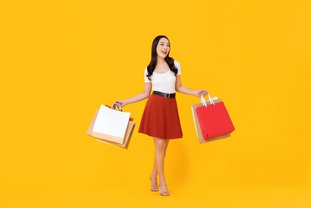 Giovane bella donna asiatica che tiene i sacchetti della spesa variopinti