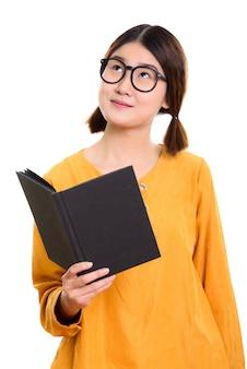 Giovane bella donna asiatica che tiene libro mentre pensa