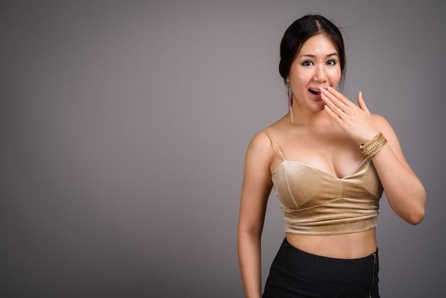 Giovane bella donna asiatica contro il muro grigio