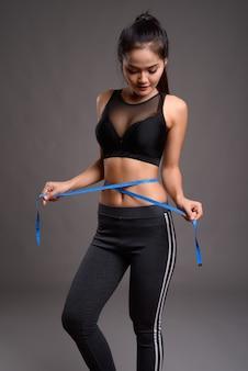 Giovane bella donna asiatica di forma fisica con nastro di misurazione della tenuta della vita sottile