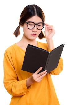 Giovane bella donna asiatica libro di lettura tenendo gli occhiali