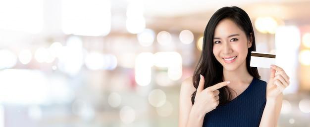 Giovane bella donna asiatica sorridente che presenta carta di credito in mano