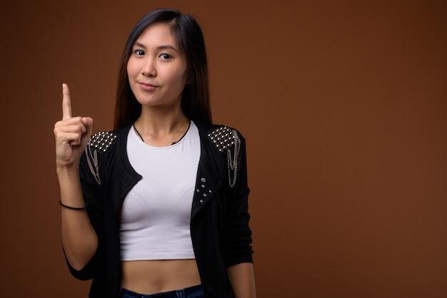 Giovane bella donna asiatica su sfondo marrone