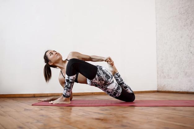 Giovane bella donna atletica che pratica asana streching dell'interno di yoga sulla stuoia rossa