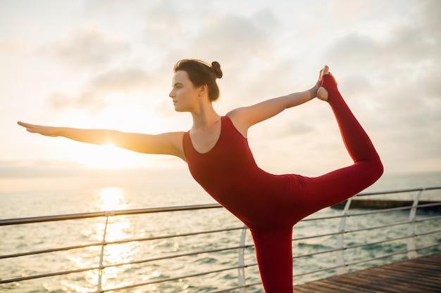 Giovane bella donna attraente sottile che fa yoga al mattino all'alba dal mare, stile di vita sano