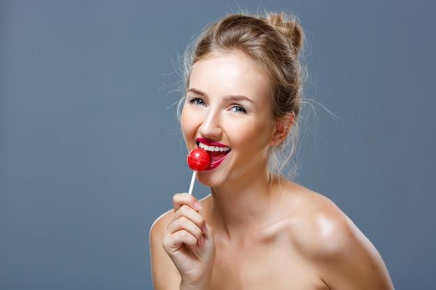 Giovane bella donna bionda che mangia lecca-lecca