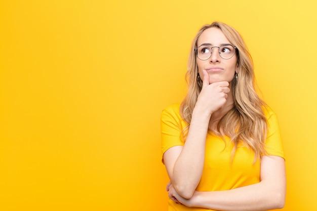 Giovane bella donna bionda che pensa, si sente dubbiosa e confusa, con diverse opzioni, chiedendosi quale decisione prendere contro la parete di colore
