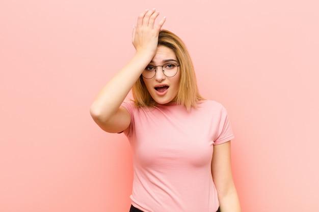 Giovane bella donna bionda che solleva il palmo alla fronte pensando oops, dopo aver fatto uno stupido errore o aver ricordato, sentendosi muta contro la parete piatta rosa