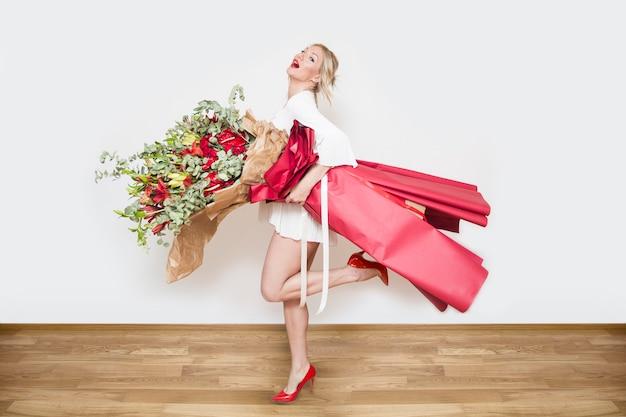 Giovane bella donna bionda che tiene grande mazzo di fiori colorati contro il muro