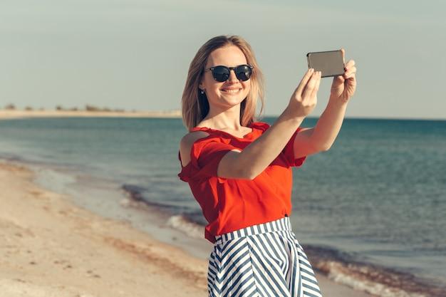 Giovane bella donna bionda con il cellulare sulla spiaggia