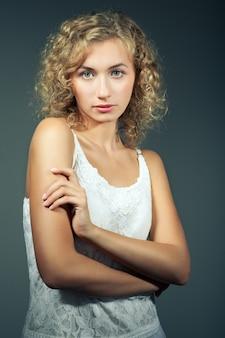 Giovane bella donna bionda esile con capelli ricci in vestito sexy bianco che sta e che esamina macchina fotografica sopra fondo grigio