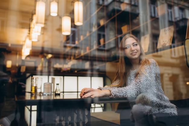 Giovane bella donna bionda seduta in un bar nel centro della città
