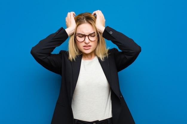 Giovane bella donna bionda sentirsi stressata e ansiosa, depressa e frustrata con un mal di testa, alzando entrambe le mani a testa contro la parete piatta