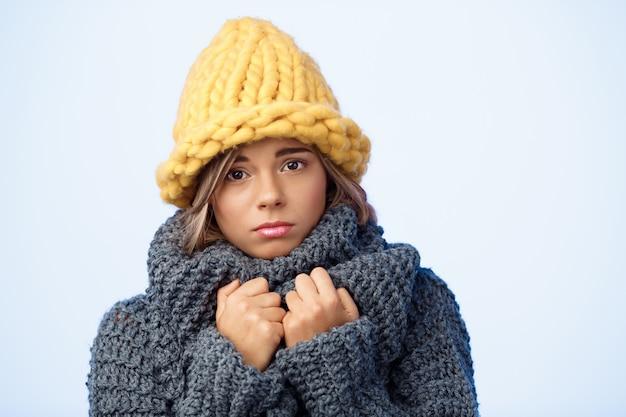 Giovane bella donna biondo bella triste in cappello e maglione tricottati sul blu.