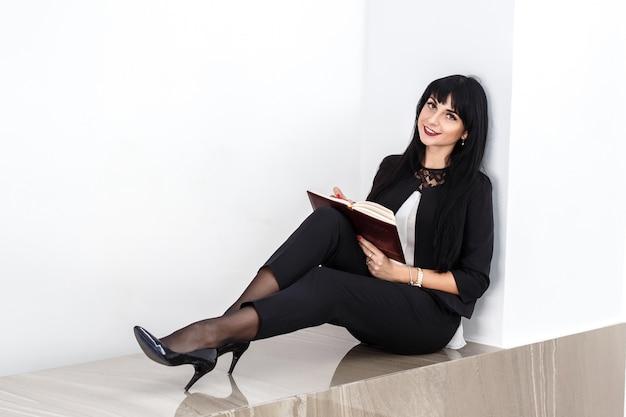 Giovane bella donna bruna felice in possesso di un notebook vestito in tailleur nero seduto su un pavimento in ufficio, sorridendo, guardando a porte chiuse.