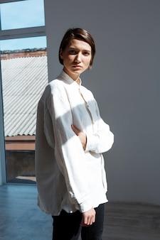 Giovane bella donna castana che posa controllando parete bianca