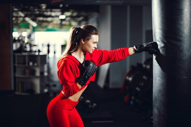 Giovane bella donna castana esile adatta che inscatola in abiti sportivi. luce fioca scura.