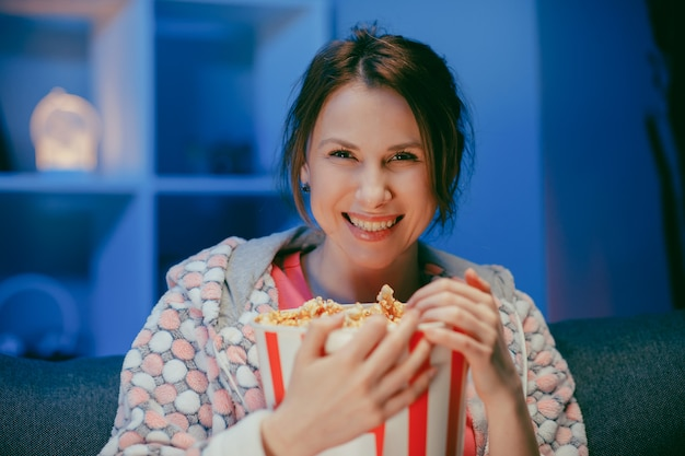 Giovane bella donna caucasica allegra che guarda il film della commedia che mangia popcorn