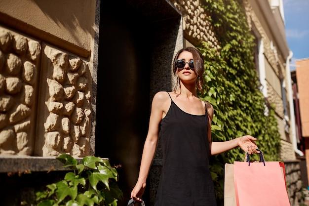 Giovane bella donna caucasica castana alla moda in occhiali da sole e vestito nero che lascia negozio con i sacchetti della spesa nelle mani e l'espressione rilassata del fronte. concetto di stile di vita