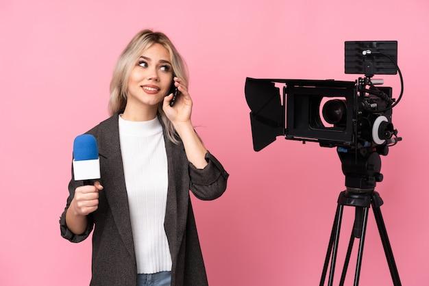 Giovane bella donna caucasica del reporter sopra la parete rosa