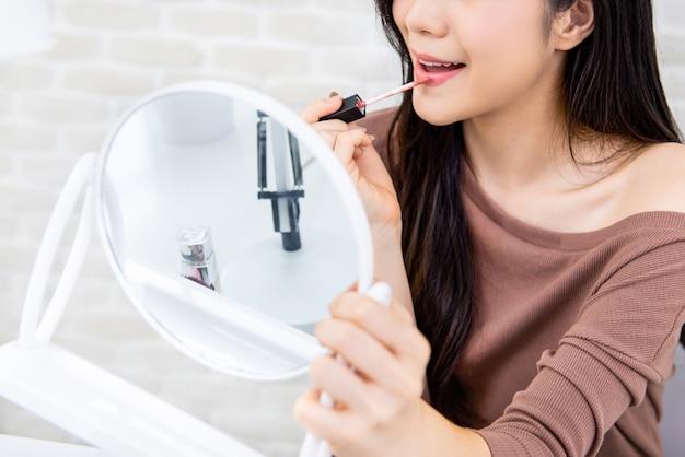 Giovane bella donna che applica la crema del rossetto alla sua bocca