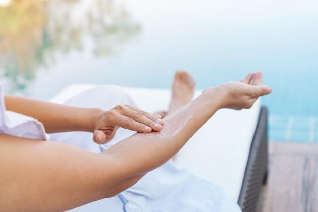 Giovane bella donna che applica protezione solare o lozione solare nel suo corpo per protezione solare della pelle alla piscina. ragazza bruna godendo le vacanze estive.