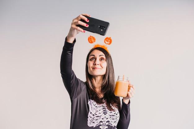 Giovane bella donna che beve il succo di arancia e che prende un selfie con il telefono cellulare. indossa un costume scheletro bianco e nero. concetto di halloween. in casa