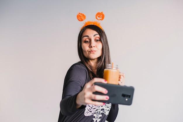 Giovane bella donna che beve il succo di arancia e che prende un selfie con il telefono cellulare. indossa un costume scheletro bianco e nero. concetto di halloween
