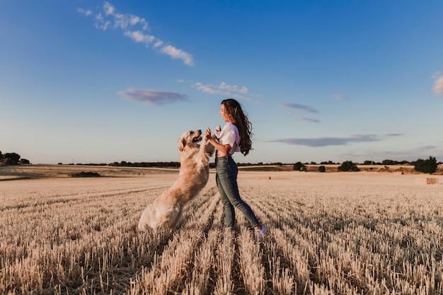Giovane bella donna che cammina con il suo cane golden retriever su un campo giallo al tramonto