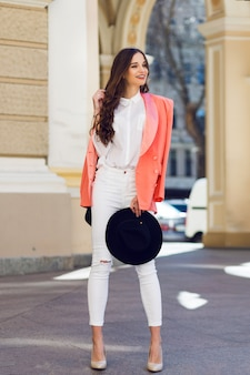 Giovane bella donna che cammina nella città vecchia in abiti glamour casual alla moda, giacca rosa. stagione primaverile o autunnale, tempo soleggiato. intera lunghezza.