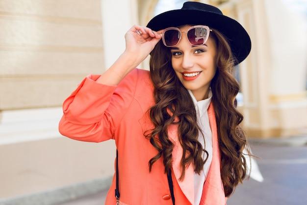 Giovane bella donna che cammina nella città vecchia in abiti glamour casual alla moda, giacca rosa. stagione primaverile o autunnale, tempo soleggiato.