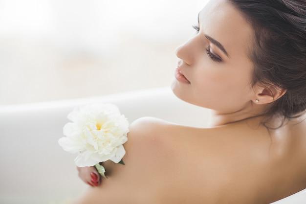 Giovane bella donna che cattura bagno con fiori e latte