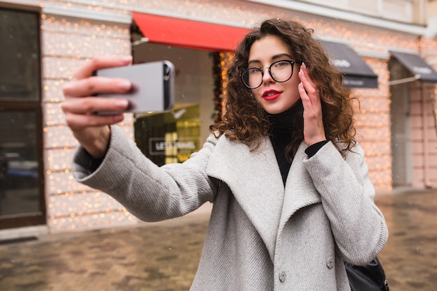 Giovane bella donna che cattura foto seflie utilizzando smartphone, autunno street city style, cappotto caldo, occhiali, felice, sorridente, tenendo il telefono in mano, capelli ricci
