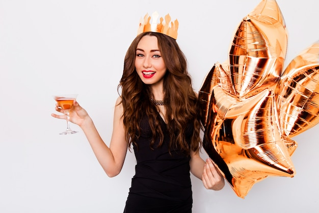Giovane bella donna che celebra in abito nero sorriso e in posa con cocktail in mano e palloncini di purezza.