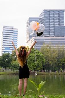 Giovane bella donna che celebra laurea al parco
