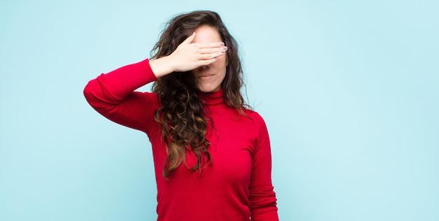 Giovane bella donna che copre gli occhi con una mano sentendosi spaventata o ansiosa, chiedendosi o aspettando ciecamente una sorpresa contro la parete blu