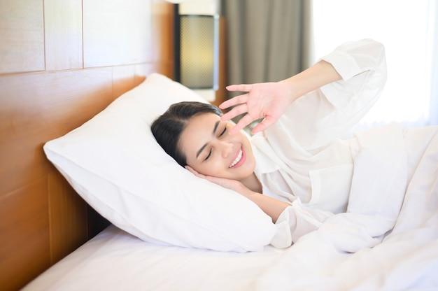 Giovane bella donna che dorme nel suo letto a casa