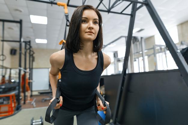 Giovane bella donna che fa crossfit con cinghie di fitness