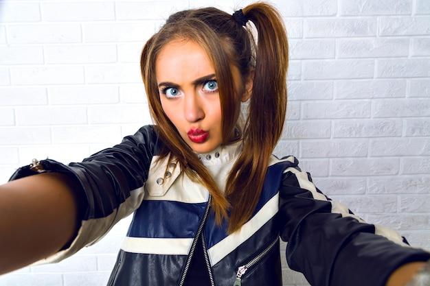 Giovane bella donna che fa selfie, trucco luminoso, bella custodia, due graziose code di cavallo, giacca di pelle da motociclista, muro urbano grunge. divertirsi da solo, fare foto per i suoi amici.