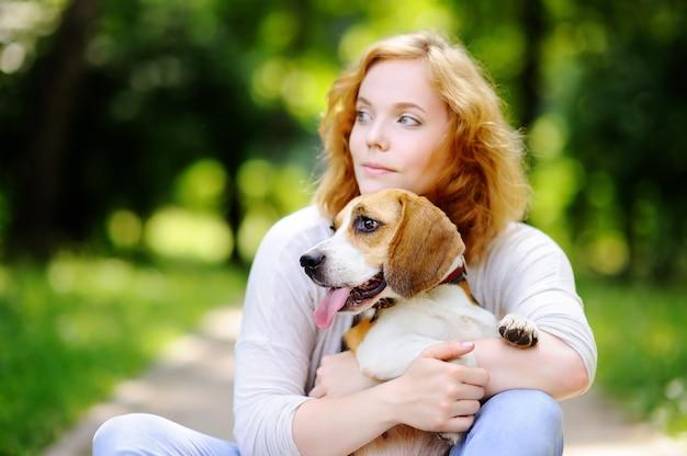 Giovane bella donna che gioca con il cane beagle nel parco estivo