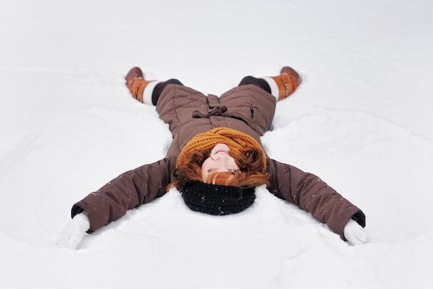Giovane bella donna che gioca nella neve