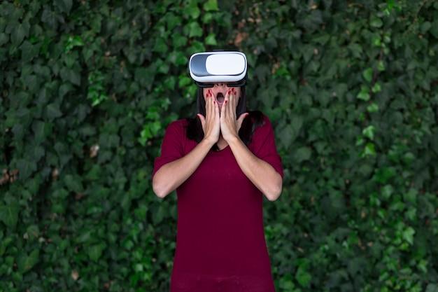 Giovane bella donna che gode della cuffia avricolare di vetro di realtà virtuale o degli occhiali 3d
